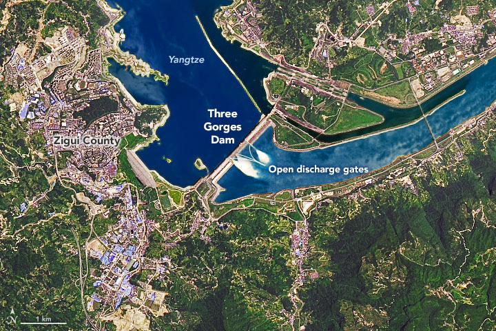 Imagem de satélite mostra a barragem de Três Gargantas e os portões abertos na tentativa de regular o fluxo da água. O nível do reservatório bateu o recorde da história em meados de julho após as chuvas de monções. Crédito: Earthobservatory/NASA.